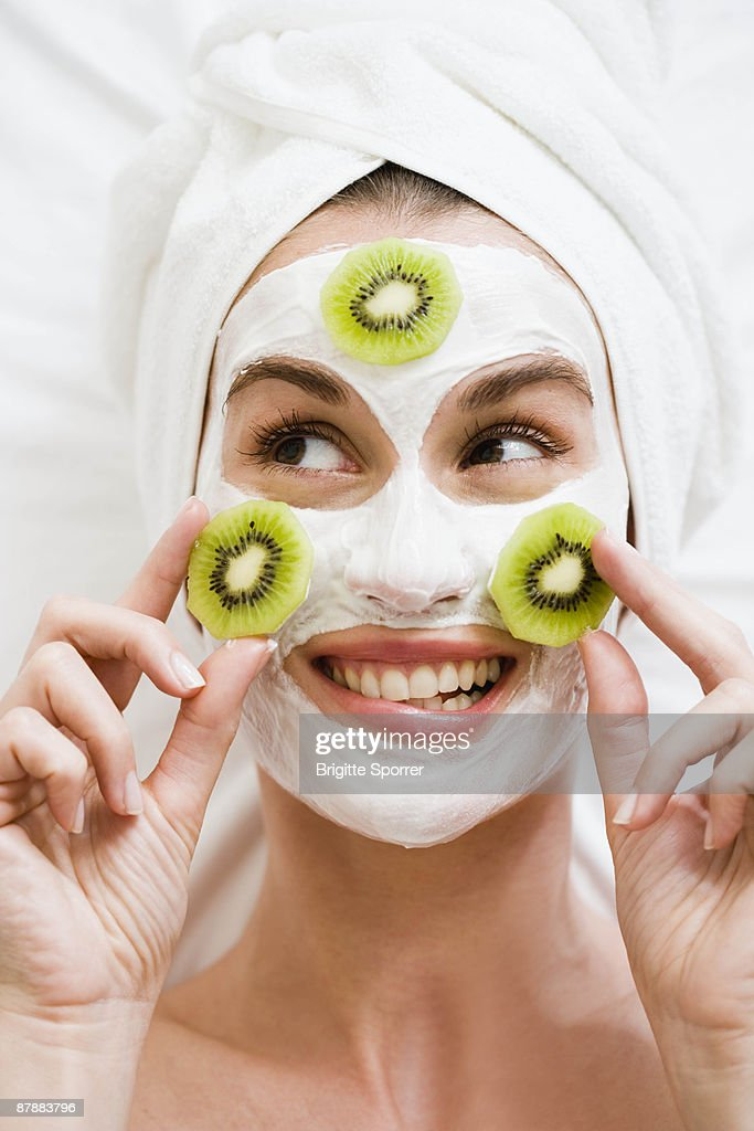 Woman with face mask and kiwi fruit : Stock Photo