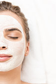 spa therapy for woman with closed eyes receiving facial mask