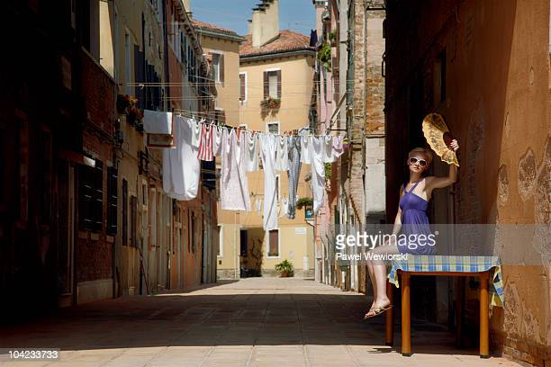 Woman with fan sitting on table