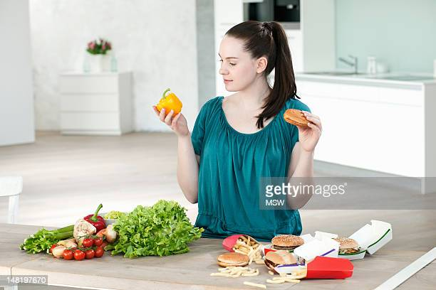 Woman with fast food and vegetables