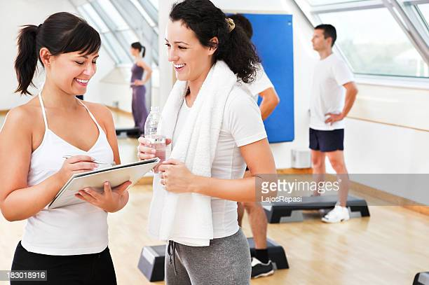Woman with female personal trainer at the gym