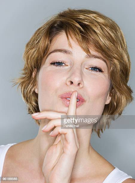 Woman with finger on lips, close-up