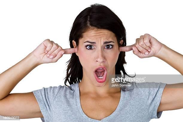 Femme avec les doigts dans ses oreilles