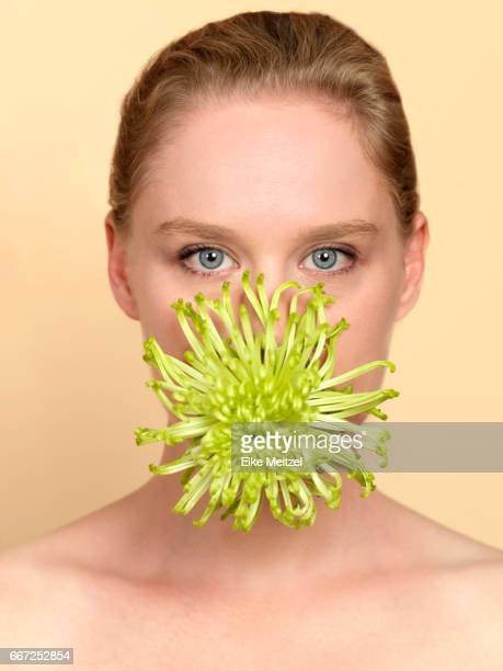woman with flower in her mouth
