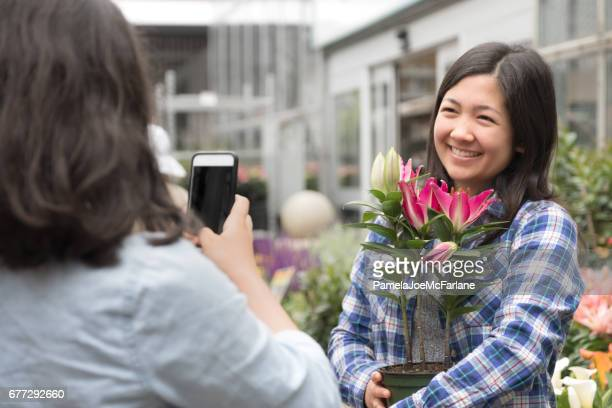 Woman with Flowering Plant Posing for Cellphone Photo in Nursery