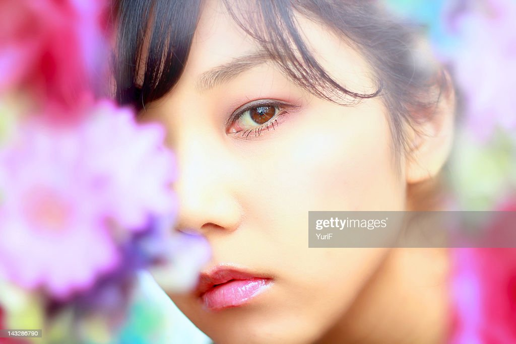 Woman with flowers in foreground : Stock Photo