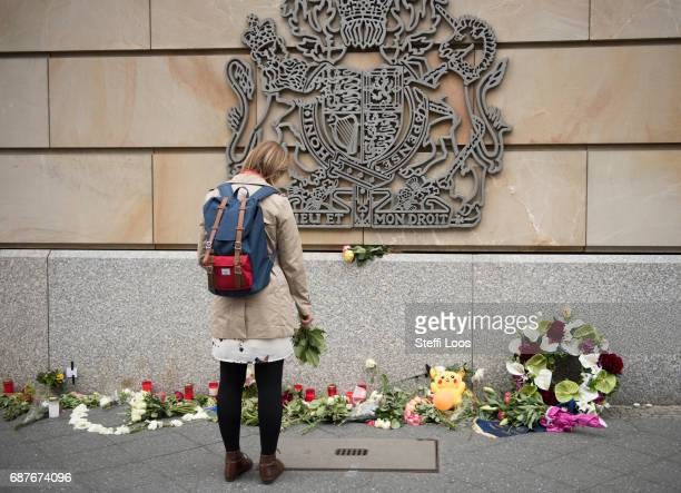 A woman with flowers in her hand stands in front of British Embassy on May 24 2017 in Berlin Germany An explosion occurred at Manchester Arena as...