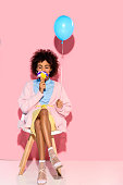 african american woman with flowers in ice cream cone and balloon in hands on pink wall backdrop