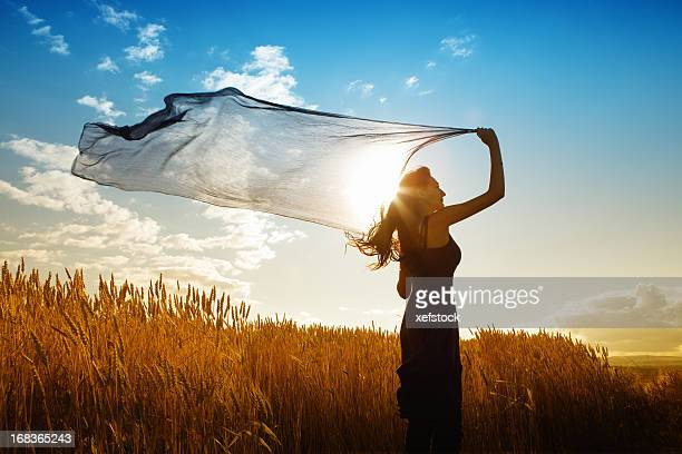 Woman with flying scarf in wheat field