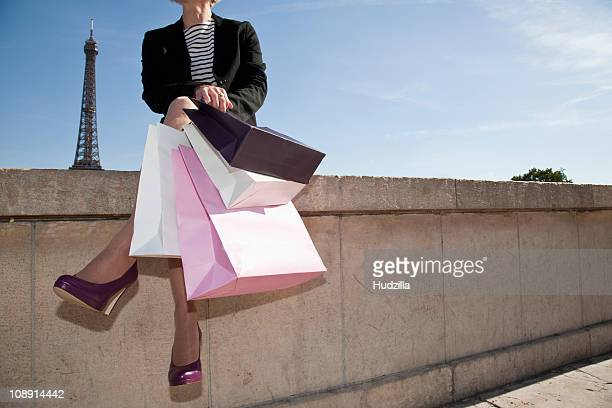 A woman with four shopping bags sitting on a wall  in Paris, France