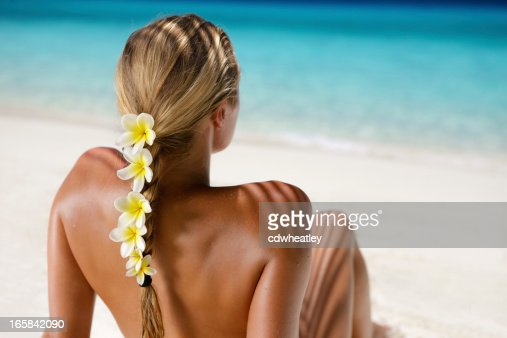 woman with frangipani in hair sunbathing at the Caribbean beach
