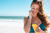 Beautiful young woman in blue bikini at beach applying sunscreen on face for protection on a sunny day. Mature woman with freckles and red hair enjoying summer holiday while applying suntan lotion. Po