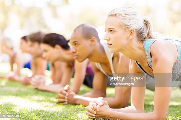Woman With Friends In Plank Position In Bootcamp