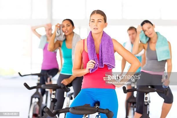 女性と友人たちのスピンバイクに座って