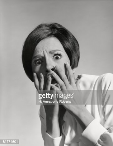 Woman with frightened expression, holding hands up to face. : Stock Photo