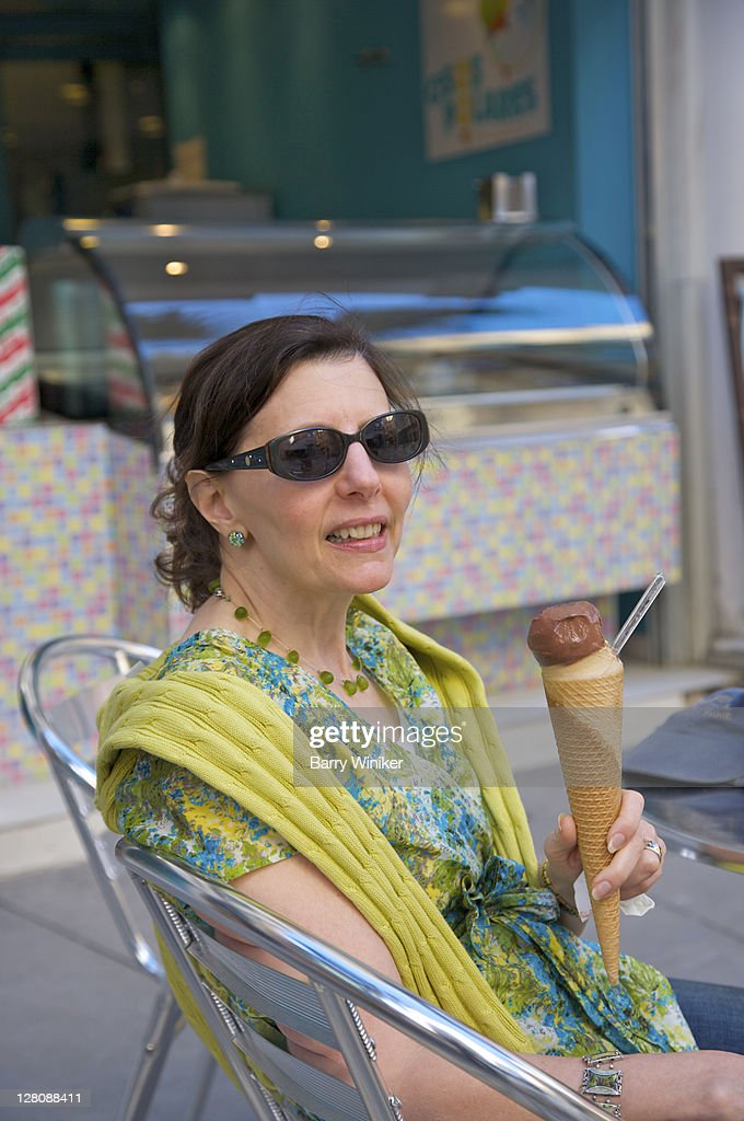 Woman with gelato in sugar cone at cafe on street of Malaga, Costa del Sol, Andalucia, Spain : Stock Photo