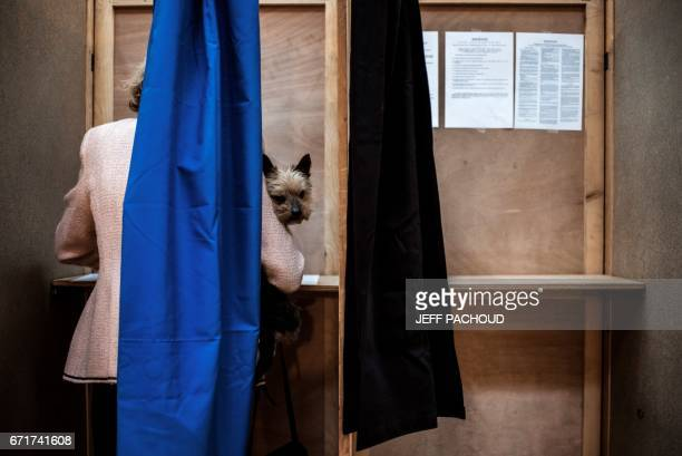 TOPSHOT A woman with ger dog votes at a polling station in Lyon on April 23 during the first round of the Presidential elections / AFP PHOTO / JEFF...