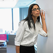 Woman with glass listening through wall in office