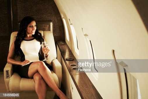 Woman with glass of champagne on private jet : Stock Photo