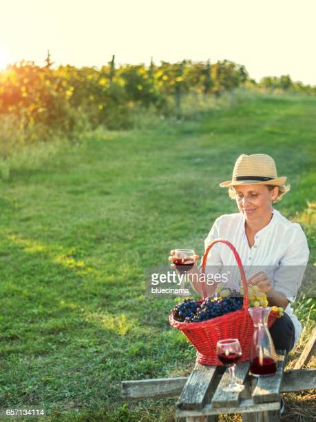 Woman with glass of wine in the vineyard