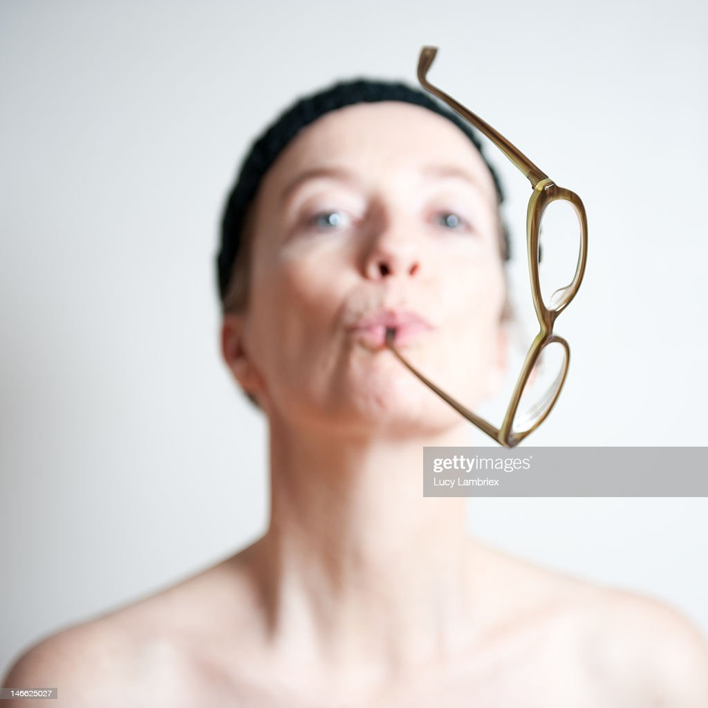 Woman with glasses in her mouth