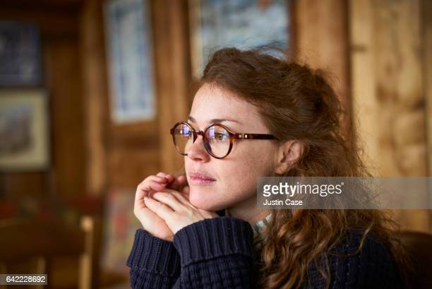 woman with glasses looking out of window in a cosy wooden lodge