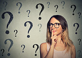 Thinking business woman with glasses looking up at many questions mark isolated on gray wall background