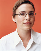 Woman with glasses standing in front of orange background