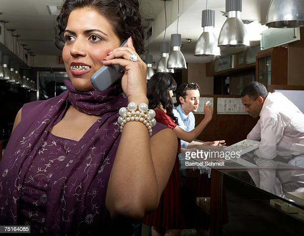 Woman with gold teeth using mobile phone in department store