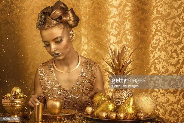 woman with golden body painting having golden dinner