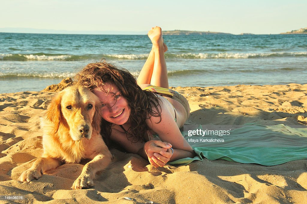Woman with golden retriever dog laying on beach : Stock Photo