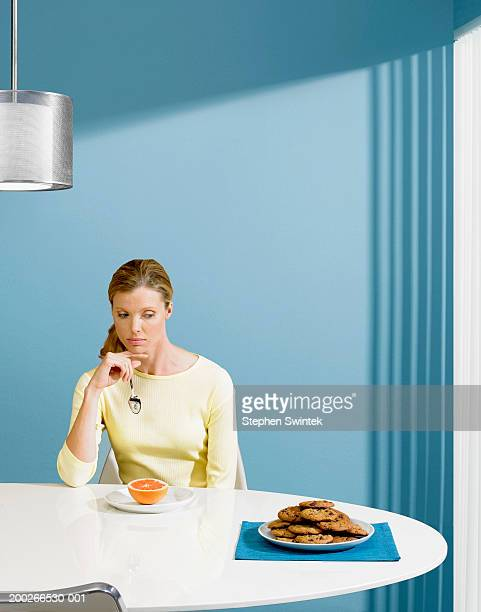 Woman with grapefruit looking at plate of cookies