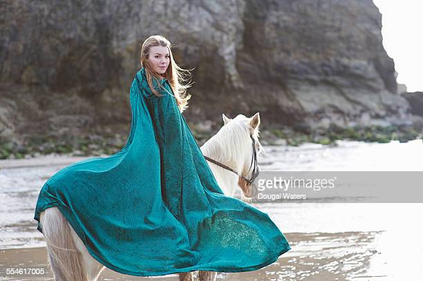 Woman with green cloak riding horse at beach