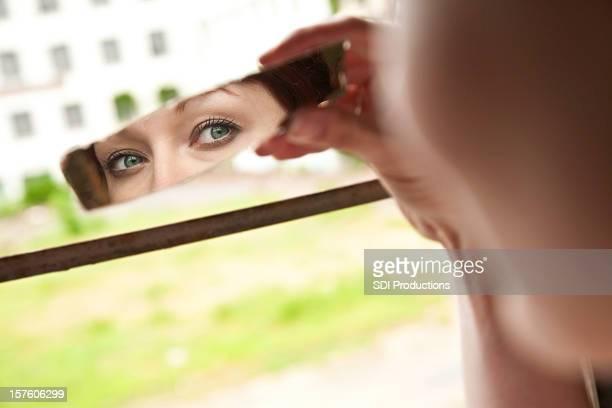 Frau mit grünen Augen schaut in Broken Stück Spiegel