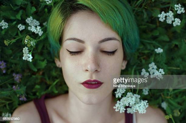Woman with green hair lays in grass with white flowers