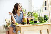 Beautiful woman sitting with healthy green food and drinks at home. Vegan meal and detox concept