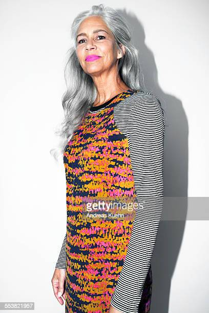 Woman with grey hair and pink lipstick.