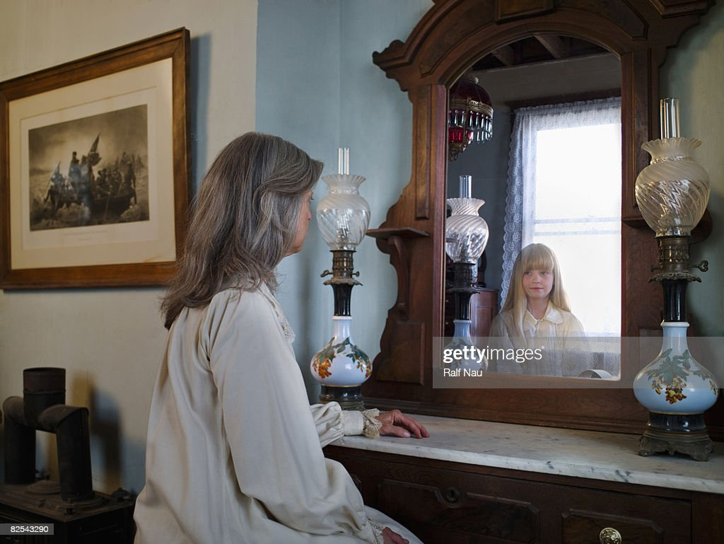 Woman with grey hair looking at herself in mirror : Stock Photo