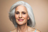 Woman with grey hair smiling, portrait.