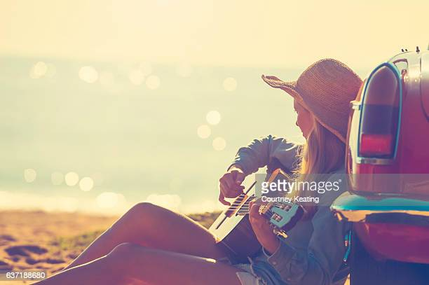 Woman with guitar leaning on a car.