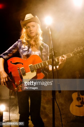 Woman with guitar on stage