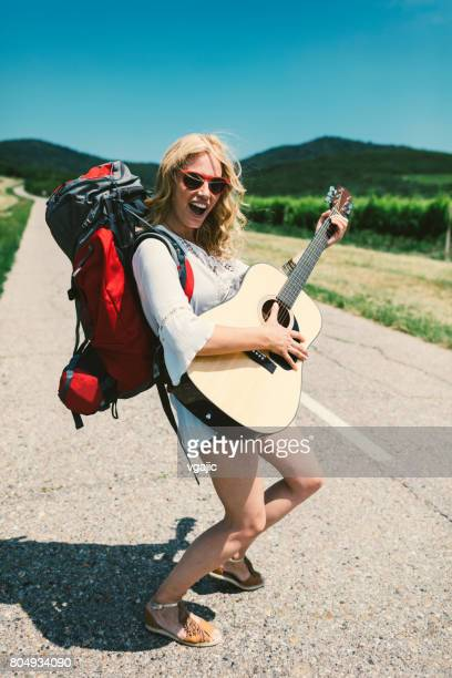 Woman with guitar on the road