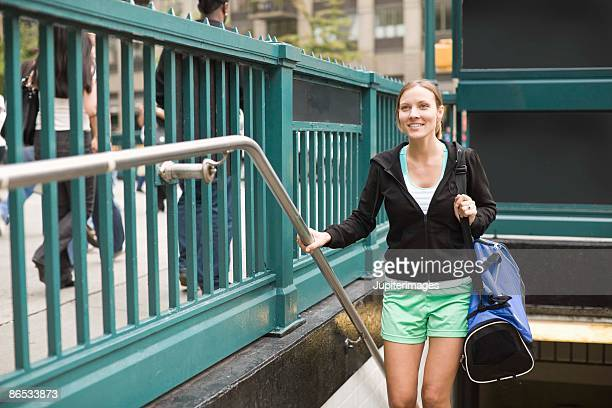 Woman with gym bag walking out of subway station