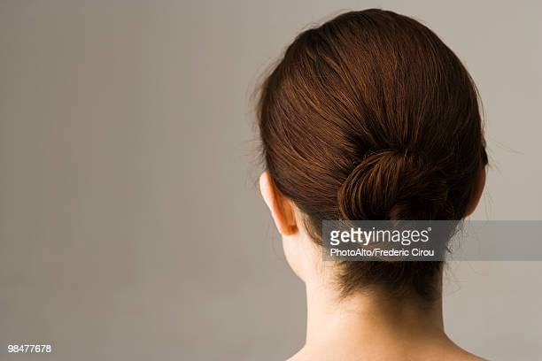Woman with hair arranged in chignon, rear view