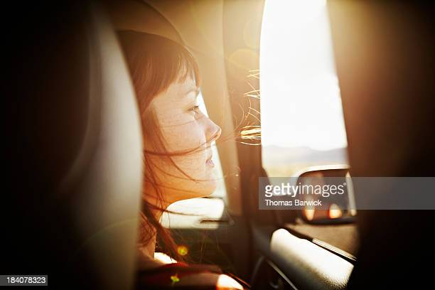 Woman with hair blowing looking out window of car
