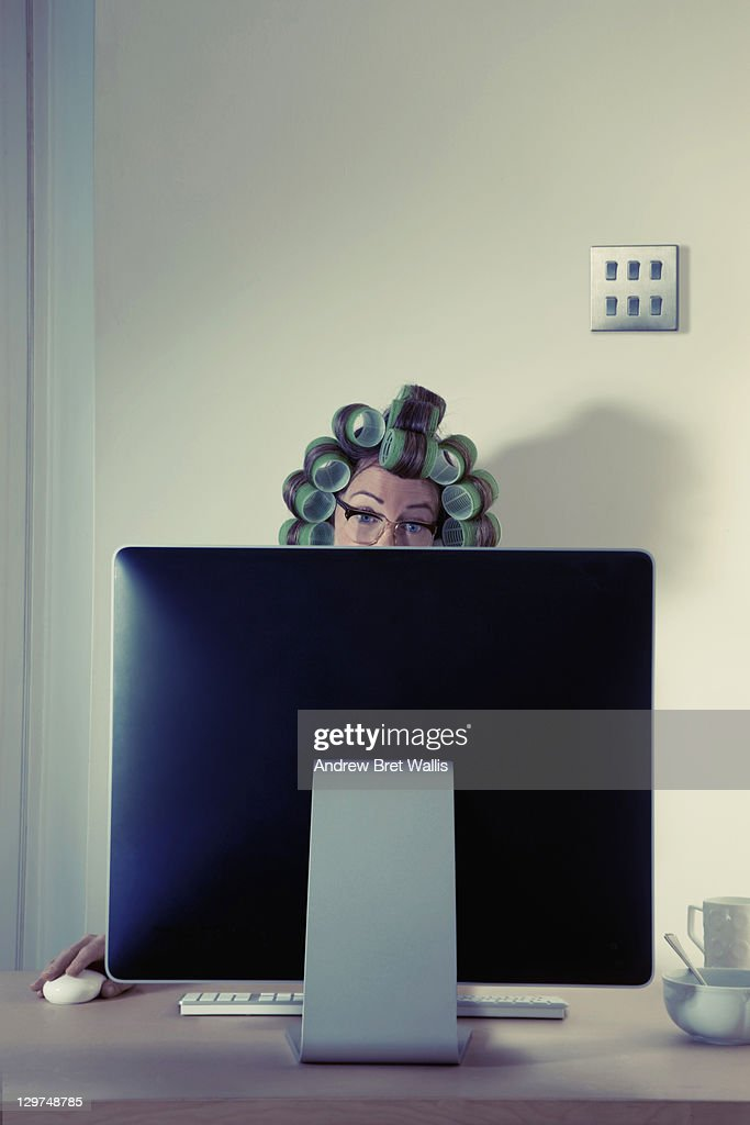 Woman with hair in rollers using computer at home : Stock Photo