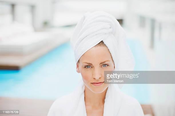 Femme avec les cheveux enveloppé dans une serviette au bord de la piscine