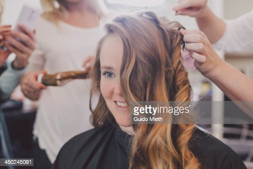 Woman with hairdressers around.