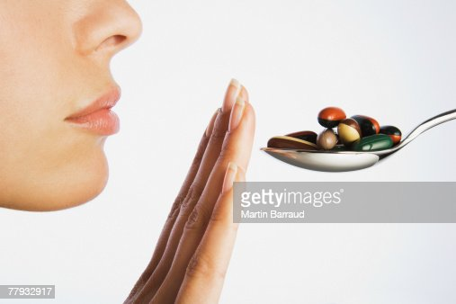 Woman with hand blocking spoonful of pills
