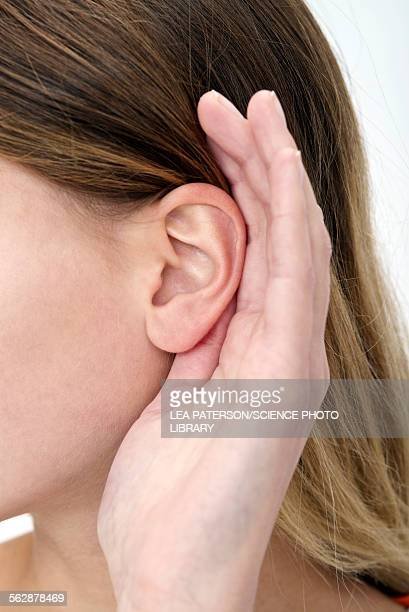 Woman with hand cupping ear
